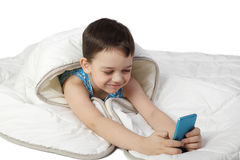 Little boy under blanket plays with smart phone Stock Photos
