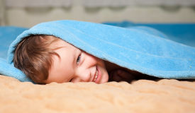 Little boy under a blue blanket Royalty Free Stock Photos