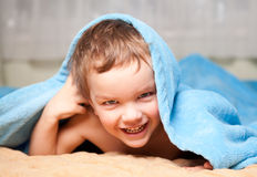 Little boy under a blue blanket Stock Photo