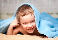 Little boy under a blue blanket Stock Photo
