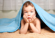 Little boy under a blue blanket Royalty Free Stock Images