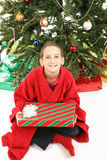 Little Boy Under Christmas Tree with Gift. Cute little boy on Christmas morning, eager to open his gifts royalty free stock photo