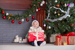 Little boy under tree at Christmas. Child found gift under tree for Christmas Royalty Free Stock Images