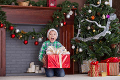 Little boy under tree at Christmas. Child found gift under tree for Christmas Stock Photo