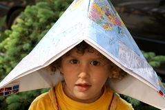 Little boy under world map cap. Curly boy seat & Chess board stock photography
