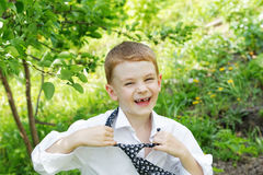 The little boy unties a tie Royalty Free Stock Photos