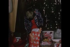 Little boy unwrapping Christmas presents stock footage