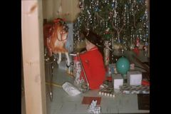 Little boy unwrapping presents under Christmas tree stock footage