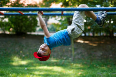 Little boy upside down at playground. Little boy in red cap upside down at playground, outdoor activity, dangerous Stock Images