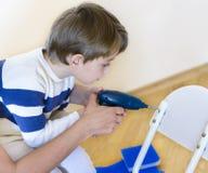 Little Boy usando a ferramenta diy que está sendo ajudada pelo pai Imagem de Stock Royalty Free