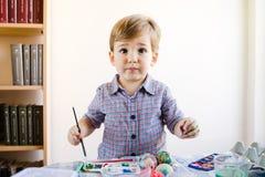 Little Boy usando i colori di acqua per dipingere a casa immagine stock
