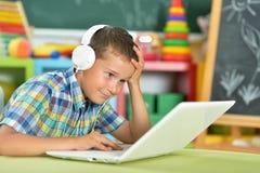 Little Boy usando la computadora portátil Foto de archivo