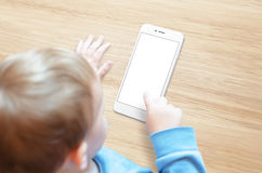 Little boy use mobile phone. White, blank, isolated screen for mockup Royalty Free Stock Images