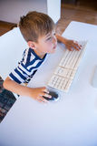 Little boy using computer in the living room Royalty Free Stock Photos