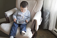 Little boy using a digital tablet sit on the living room Stock Photos