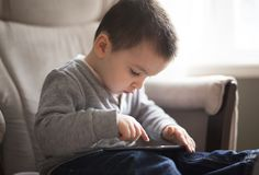 Little boy using a digital tablet sit on the living room. A Little boy using a digital tablet sit on the living room Stock Photo
