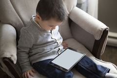 Little boy using a digital tablet sit on the living room Royalty Free Stock Photos