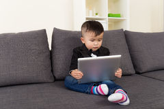 Little boy using digital tablet and sitting on sofa Royalty Free Stock Photography