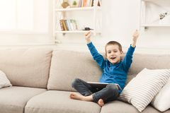 Little boy using digital tablet on sofa at home. Little boy watching football from digital tablet. Gadgets and technology concept, playing online game while Stock Photos