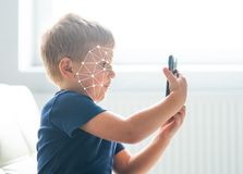 Little boy using face id authentication. Kid with a smartphone. Digital native children concept. Little boy using face id authentication. Kid with a smartphone royalty free stock photography