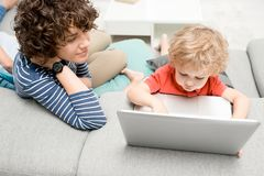 Little Boy Using Laptop. High angle portrait of young mother teaching her toddler son use laptop while sitting on sofa in living room at home Stock Photos