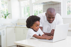 Little boy using a laptop with his father Stock Photo