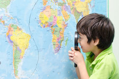 Little boy using magnify looking on map. In classroom Royalty Free Stock Photo