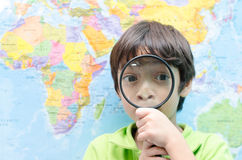 Little boy using magnify looking on map Stock Photography