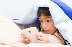 Little boy using mobile under blanket Stock Photos