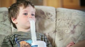 Little boy using nebulizer to inhale medicine, close up, stock footage Stock Photography
