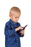 Little boy using smartphone. Portrait of a cute little boy using smartphone in denim blue shirt isolated on white background Stock Image