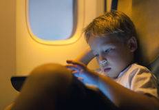 Little boy using tablet computer during flight. Close-up shot of a little boy playing on touch pad during in the plane. Child looking tired or bored Royalty Free Stock Images