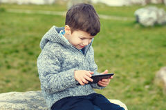 Little boy using tablet outdoor Royalty Free Stock Photos