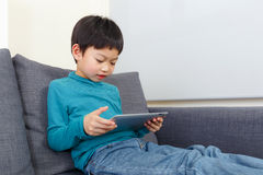 Little boy using tablet and sitting on sofa Stock Image
