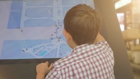 Little boy using a touch screen of interactive information stand in the supermarket. Child is using a touch screen of interactive information stand in the stock footage
