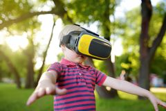 Little boy using virtual reality headset outdoor. VR, VR glasses, augmented reality experience royalty free stock photos