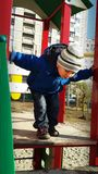 Little boy verifying height of slides. Two years old kid playing at the playground. He climbed up the slide and now checking out its height looking down. He is Royalty Free Stock Photo