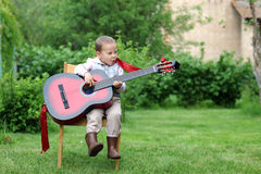 Little boy very passionary play in guitar outdoors Stock Photos