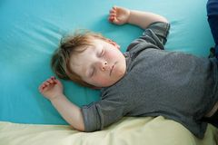 Little Boy. Very tired little boy crashed out asleep on his bed Royalty Free Stock Photography