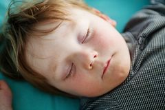 Little Boy. Very tired little boy crashed out asleep on his bed Stock Photo