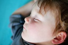 Little Boy. Very tired little boy crashed out asleep on his bed Stock Photography