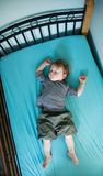 Little Boy. Very tired little boy crashed out asleep on his bed Royalty Free Stock Photo