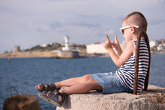 Little boy in vest and shorts sitting on breakwater on background of sea and shore. Small boy in a vest and shorts sitting on a breakwater on the background of Royalty Free Stock Photo
