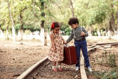 A little boy in vintage clothes and a little cute girl in a vintage dress carry a vintage suitcase along the rails.  royalty free stock images