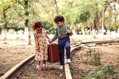 A little boy in vintage clothes and a little cute girl in a vintage dress carry a vintage suitcase along the rails.  royalty free stock image