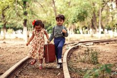 A little boy in vintage clothes and a little cute girl in a vintage dress carry a vintage suitcase along the rails.  stock photography