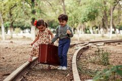 A little boy in vintage clothes and a little cute girl in a vintage dress carry a vintage suitcase along the rails.  stock photo