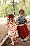 A little boy in vintage clothes and a little cute girl in a vintage dress carry a vintage suitcase along the rails.  stock image