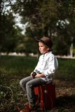 A little boy in vintage clothes is sitting on an old suitcase with a retro camera in his hands.  stock photo