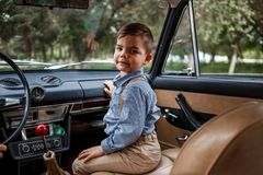 Little boy in vintage clothes sitting in retro car.  stock images